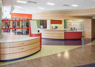 View from the main entrance doors toward the reception desk, with the card reader station and juice bar in the foreground to the left.