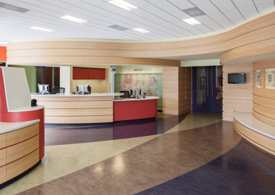 """View from the main entrance doors toward the reception desk. The entrance door to the main facility is directly ahead in the photograph. Behind the reception desk is the """"Puzzle Piece Wall"""". This artwork creates an image from a number of interlocking and interdependent pieces: a metaphor for community organizations like the YMCA."""