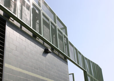 """A painted perforated metal screen enclosure surrounds the outdoor equipment yard and extends in front of the glazed block wall at the southwest corner of the building. The """"step-over"""" of the equipment screen marks the service entrance to the yard."""