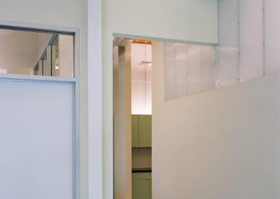 Polycarbonate panels form the upper portion of the wall along the main hall on the first level. This allows borrowed light to enter the service spaces at this level.