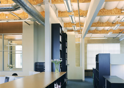 The second level spaces are primarily defined by cabinetry and custom made workstations. The exposed roof structure is visible between the quilted scrim that covered the insulation at the underside of the roof.